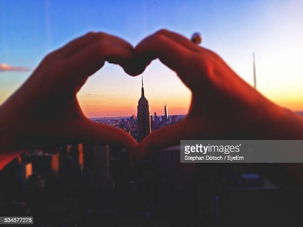 Hands Forming Heart Against Tall Building