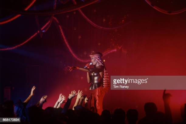 Hands from the crowd reach up to Grace Jones as she performs on stage at Hammersmith Palais London circa 1995