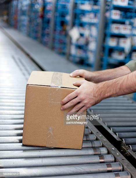 Hands getting a box off of conveyer belt