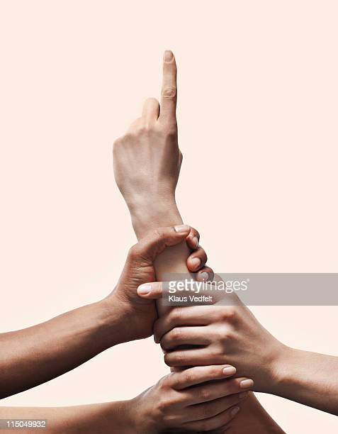 3 hands grabbing other hand with pointing finger