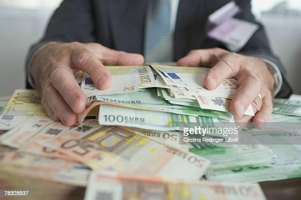 hands grabbing stack of euros - banconote euro foto e immagini stock