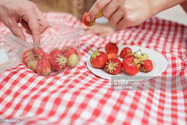 Hands grabbing strawberries,
