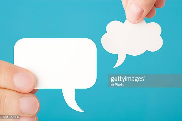 Hands hold blank speech bubbles