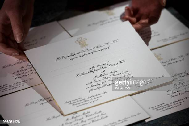 Hands hold invitations just printed at the workshop of Barnard and Westwood for Prince Harry and Meghan Markle's wedding on March 22 2018 in London...