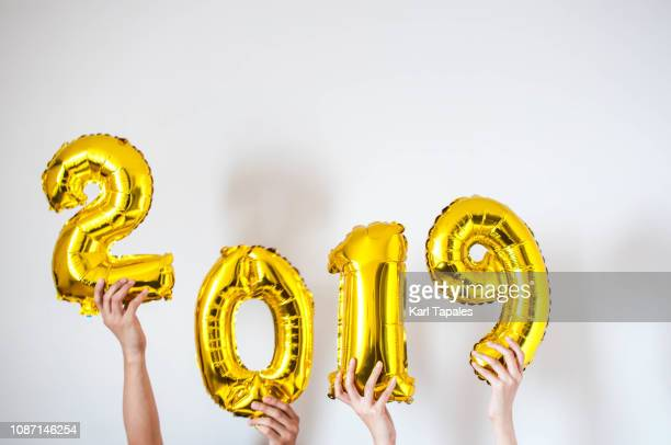 hands holding 2019 gold-colored balloon - 2019 photos et images de collection