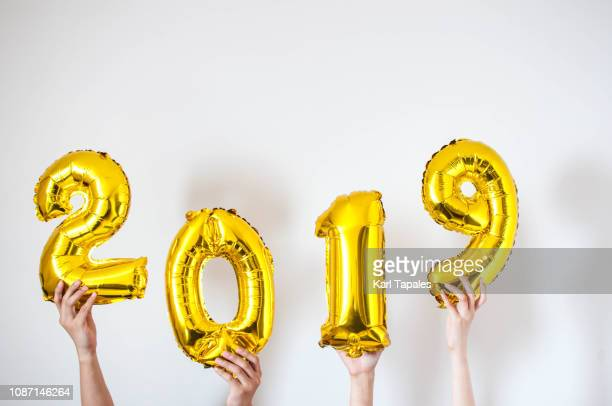 hands holding 2019 gold-colored balloon - human body part stock pictures, royalty-free photos & images