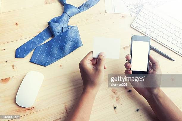 hands holding a blank card and using smart phone for business