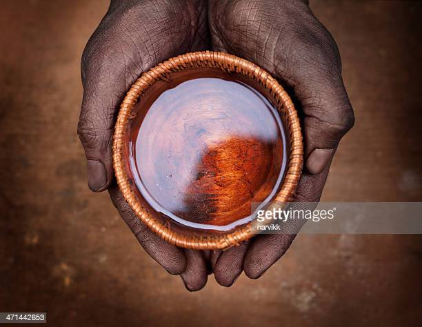 Hands holding a bowl with water