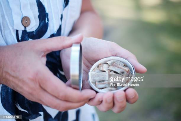 hands holding a box of snuff, snus smokeless tobacco - finn bjurvoll stock pictures, royalty-free photos & images