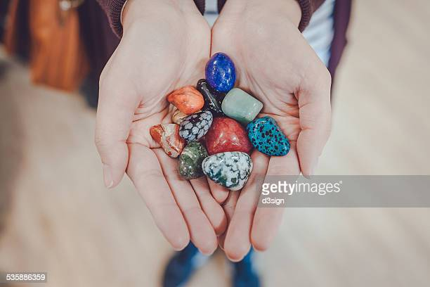 Hands holding a bunch of colourful gemstones
