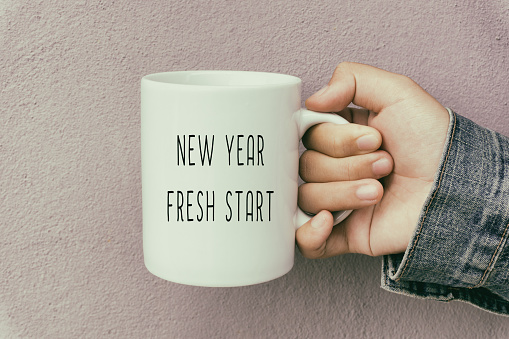 Hands Holding a Coffee Mug With Text New Year Fresh Start 880766334