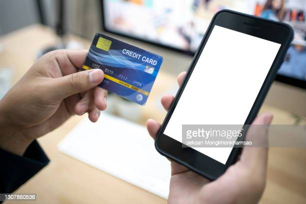hands holding a credit card and using smart phone for online shopping - fraud protection stock pictures, royalty-free photos & images