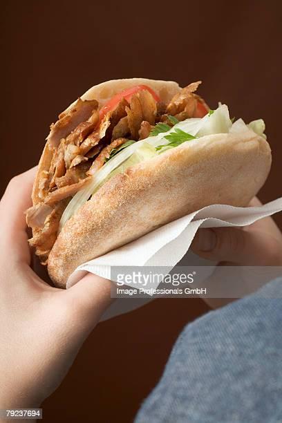 Hands holding a d?ner kebab