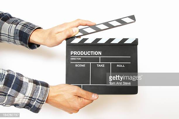 Hands holding a film production clapperboard