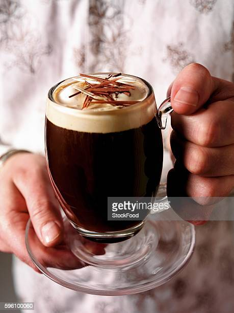 Hands holding a glass mug of Irish coffee