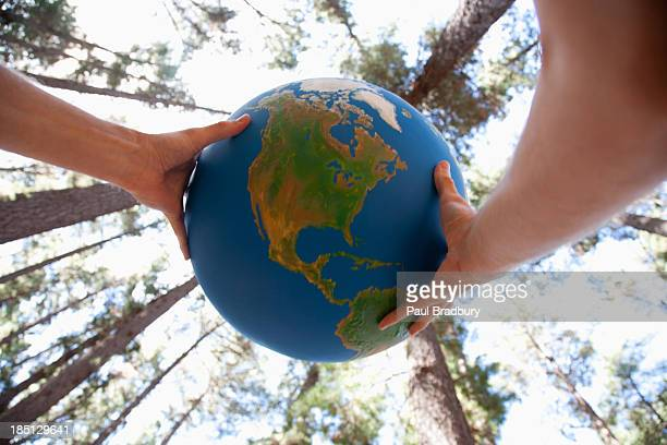 hands holding a globe - world kindness day stock photos and pictures
