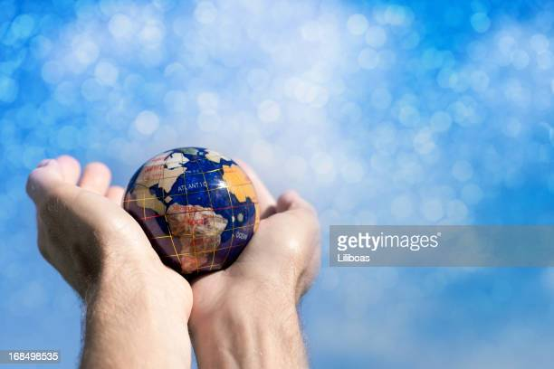 hands holding a globe towards sky - world at your fingertips stock pictures, royalty-free photos & images