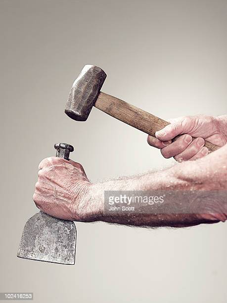 Hands holding a hammer and chisel