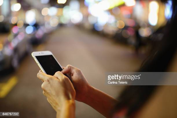 Hands holding a mobile phone on the street at night