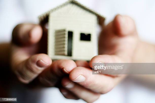 Hands holding a model of a house indicating real estate