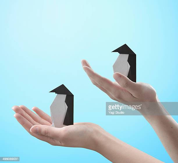 Hands holding a  origami penguins