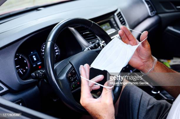 hands holding a protective mask inside a car.- stock photo. - travelstock44 stock pictures, royalty-free photos & images