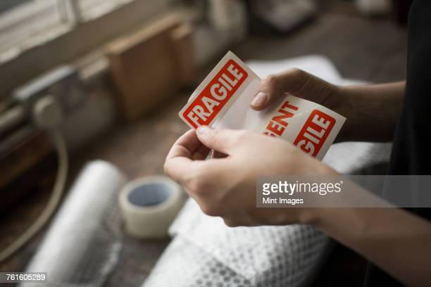 hands holding a red fragile sticker to stick it on a brown paper package on a work bench. - fragile sticker stock pictures, royalty-free photos & images