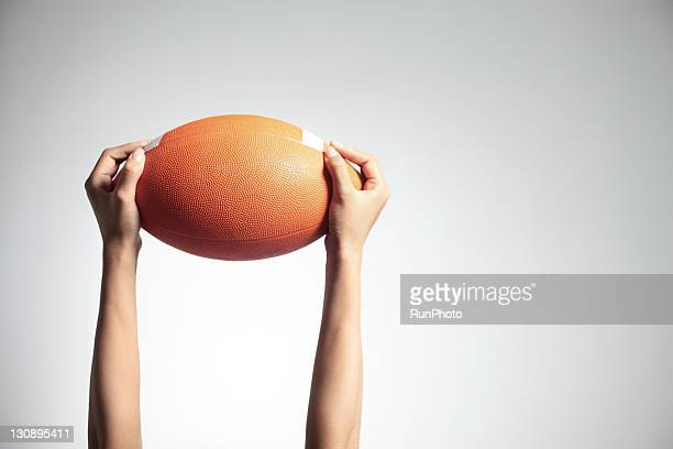 Hands holding a rugby ball,hands close-up
