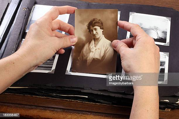 Hands holding a sepia photograph above a phot album