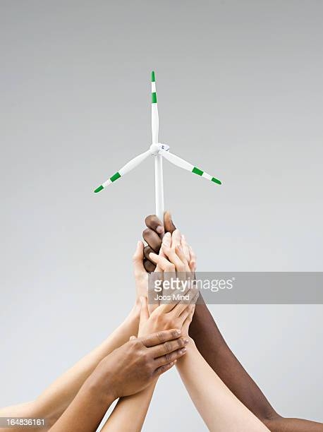Hands holding a small wind turbine