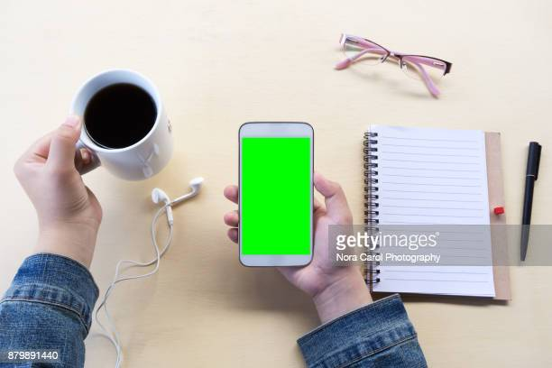 Hands Holding a Smart Phone Chroma Key Screen on Office Desk