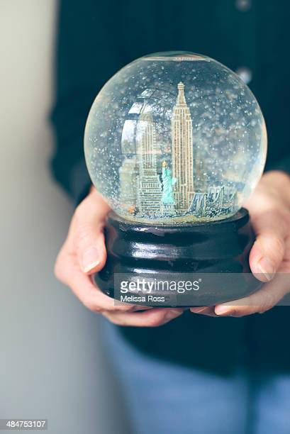 Hands holding a snow globe depicting New York City