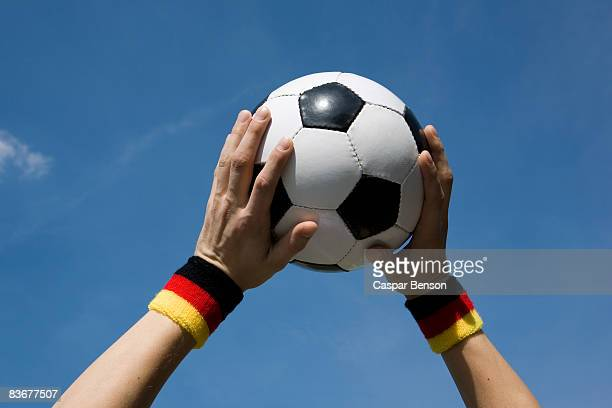 Hands holding a soccer ball in the air
