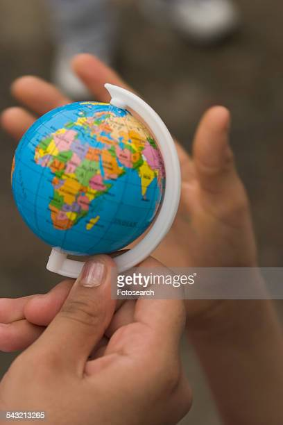 Hands holding a toy globe