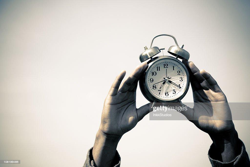Mãos segurando o relógio de alarme : Foto de stock