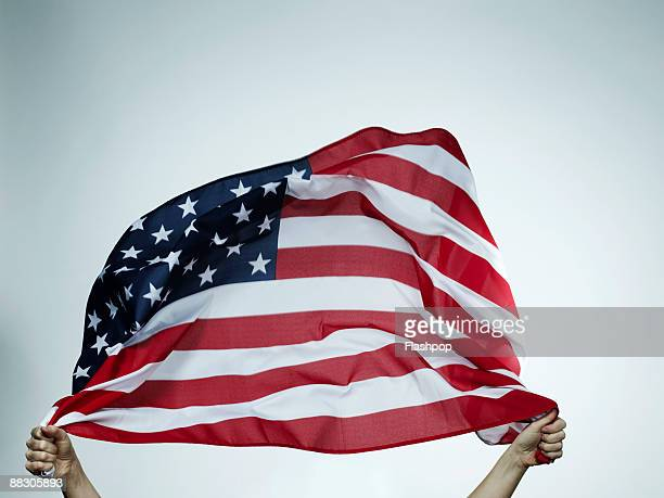hands holding american flag - american stock pictures, royalty-free photos & images
