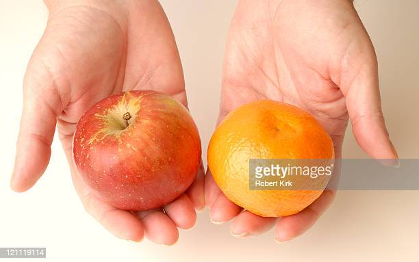 Hands holding an apple and an orange