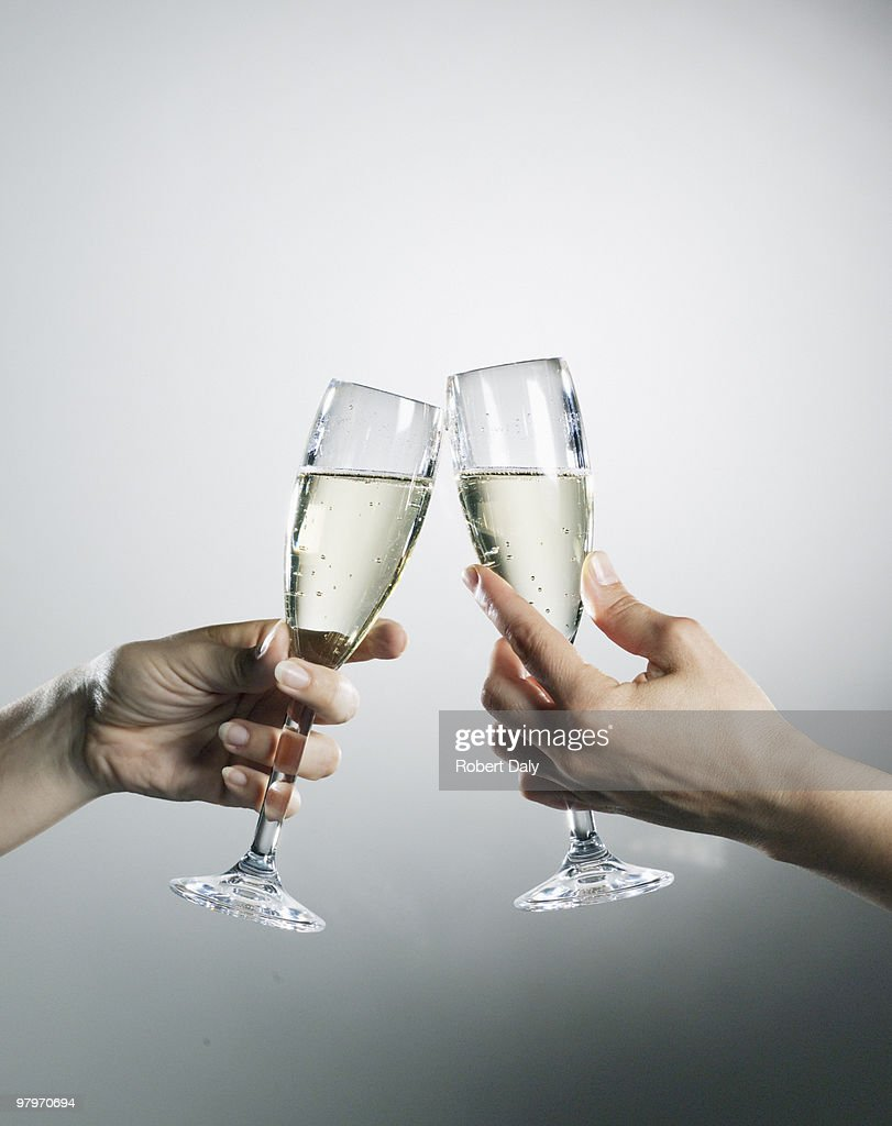 Hands holding and toasting champagne flutes : Stock Photo