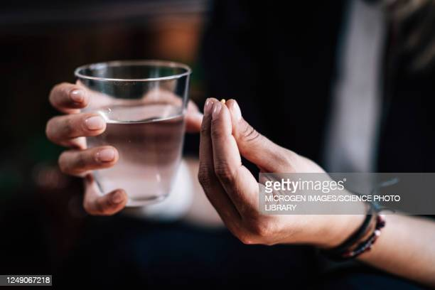 hands holding antidepressant pill and water - anti depressant stock pictures, royalty-free photos & images