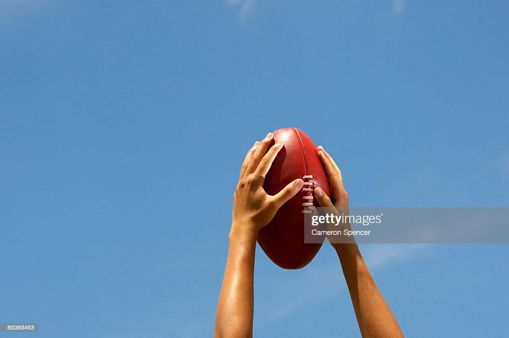 Hands holding Australian football up to the sky : Stock Photo