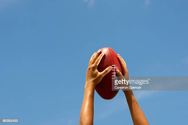Hands holding Australian football up to the sky