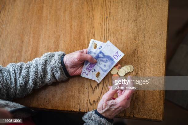 hands holding banknotes and coins - スウェーデン通貨 ストックフォトと画像