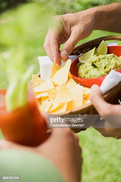 Hands holding basket of guacamole & chips and tomato drink