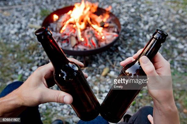 Hands holding beer bottles with campfire