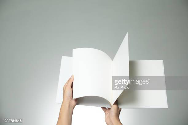 hands holding blank book - flyer leaflet stock photos and pictures