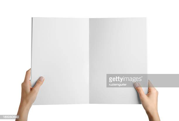 hands holding blank magazine page - magazine page stock photos and pictures