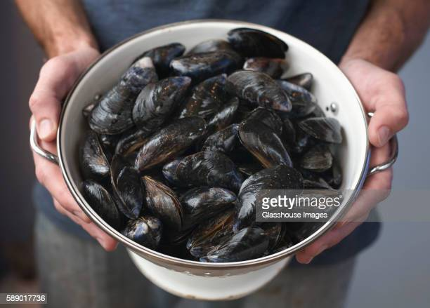 Hands Holding Bowl of Mussels