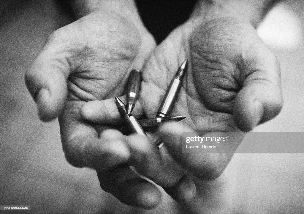 Hands holding bullets, close-up, b&w : Stockfoto