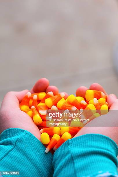hands holding candy corn heart - candy corn stock photos and pictures