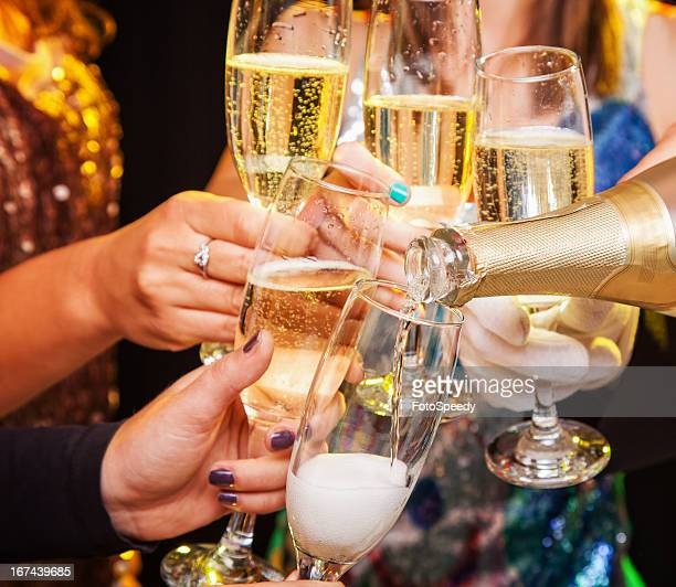 Hands holding champagne glasses during a toast